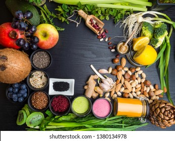 Clean eating concept over wooden background, top view, copy space. Variety of vegetables, fruit, seeds, bean, spices, superfood, herbs, condiment for vegan, raw diet or gluten free diet