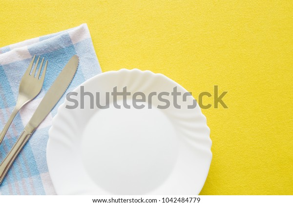 Clean, empty, white plate, fork and knife with yellow tablecloth and blue towel on a table. Cutlery concept. Flat lay. Top view.