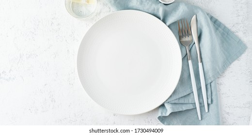 Clean empty white plate, glass of water, fork and knife on white stone table, copy space, mock up, top view, long banner