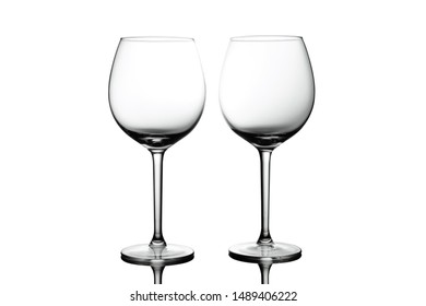 Clean Empty wine glasses with reflections on white background. Alcohol beverage card backdrop.