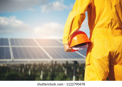 Clean Energy Concept.Electrical worker or engineer holding safety hat stand at solar panel background.Foreman wearing orange safety suit and looking at power plant
