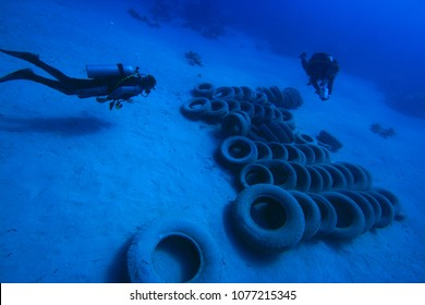Clean up of environmental pollution problem. Scuba divers remove car tyres from ocean reef