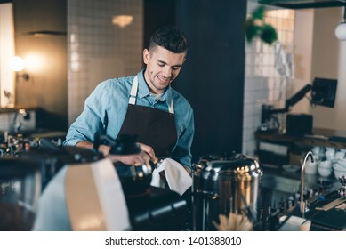 Clean equipment. Cheerful young barista standing in front of a coffee machine and smiling while drying a tamper with a towel