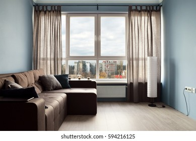 Clean family room with brown couch and large windows showing bright spring landscape in background.