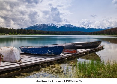 Clean fishing water. The boats are waiting to ship. fishing on blue and cold water. beautiful scenery. Mountains in the back.