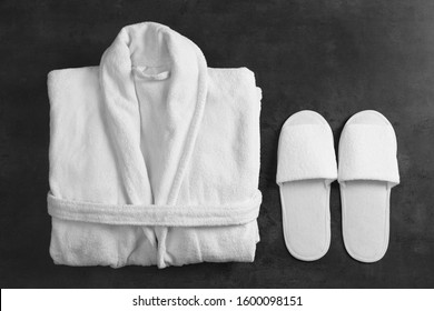 Clean folded bathrobe and slippers on black stone background, flat lay