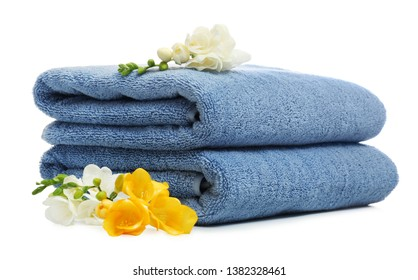 Clean folded towels with flowers on white background
