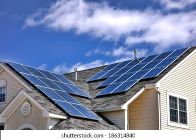 Clean green energy efficient saving source photovoltaic solar panels cells modules on residential house roof over cloudy sky producing free renewable electricity