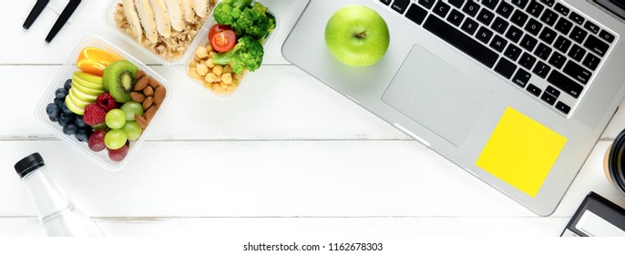 Clean healthy ready ot eat low fat food in meal box set prepared for lunch on working table with laptop computer, overhead view