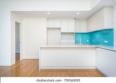 Clean interior of apartment kitchen with turquoise splashback and light coloured cabinetry.