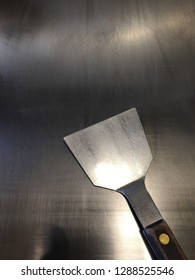 Clean iron griddle and a metal spatula used for cooking okonomiyaki or teppanyaki, Japanese food that is cooked on the iron griddle.