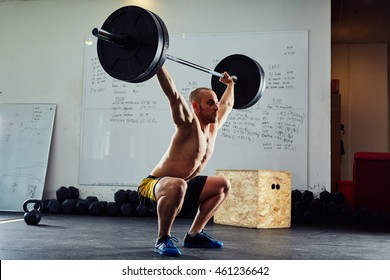 The clean and jerk exercise - young man doing weightlifting workout at the gym