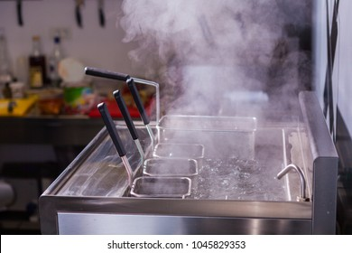 Clean kitchen. Concept fast food restaurant, equipment. Industrial kitchen. Cooking food process. Electric machine boiling water. Steam in the kitchen. Boiling pasta process. Clean kitchen steam