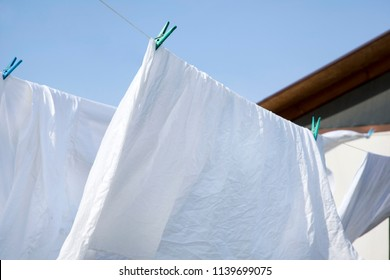Clean laundry is hung up on clothesline. Sheets secure on either clothespins