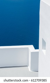 Clean lines of Greek architecture with the deep blue water in the background, taken on the island of Santorini