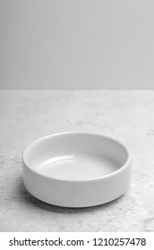 A clean little white plate on light stone background. Minimalistic kitchen, dishes. Copy space.