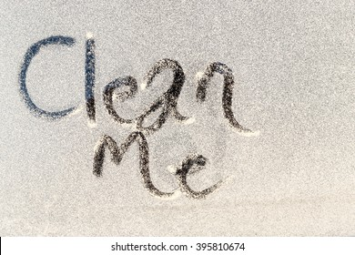 Clean Me text etched into the dirty grubby window of a window