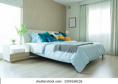 Clean modern bedroom with blue and yellow cushion setting on it. Bedroom interior with window and wood wall.