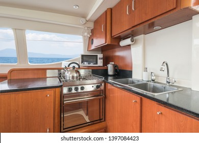 Clean and modern galley/kitchen of a private sailing catamaran with wooden cupboards, sink, oven, microwave and kettle, with Mediterranean sea view from the windows.