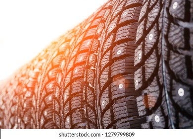 Clean new modern studded winter tires in row. Tires with spikes, close up.