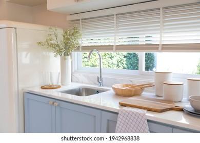 Saubere neue Spüle in stilvollen Kücheneinrichtungen am Fenster. Holzgeschirr und Keramikvase mit Blume auf der Küchentheke.