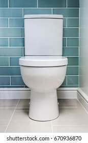 Clean new white toilet fitted against a tiled wall shot straight on.