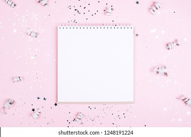 Clean note book with Silver sparkles, stars and glitters on pink background. Festive concept.
