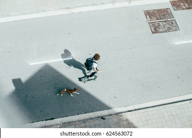 Clean, open shot of a young teenager riding skateboard with his best friend puppy in the middle of busy city street wears a trendy black backpack