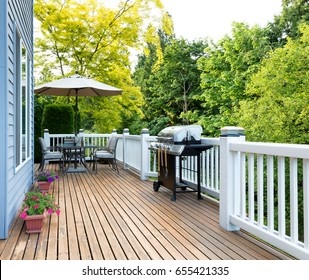Clean outdoor cedar wooden deck and patio of home with BBQ cooker and bottled beer