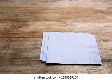 Clean paper napkins and space for text on wooden background