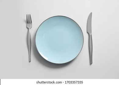 Clean plate and cutlery on light background