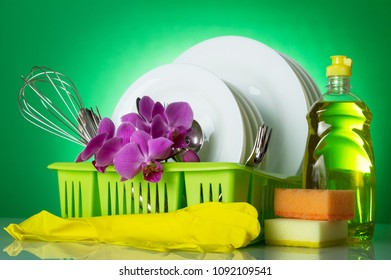 Clean plates and Cutlery in dryer, detergent, sponges and gloves, on green