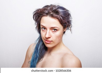 Clean portrait of a thirty year old woman with messy damaged hair dyed in violet and turquoise colors.