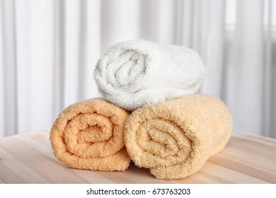 Clean rolled towels on wooden table