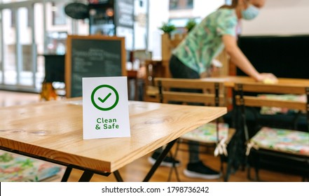 Clean and Safe sign placed on a table with waitress cleaning in the background