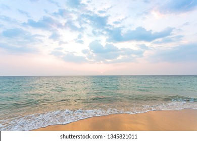 Clean sand on the beach have sea wave coming up, with soft blue sky with cloudy and small sunset