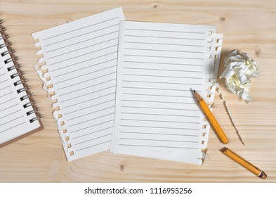 Clean sheets from notebook, broken pencil and crumpled paper against the background of a wooden table, top view