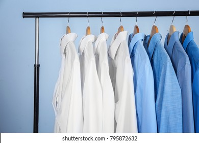 Clean shirts hanging on rack in laundry