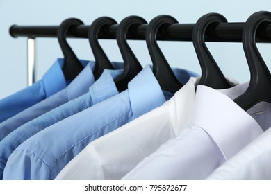 Clean shirts hanging on rack in laundry, closeup