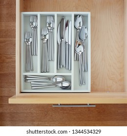 Clean silverware utensils in kitchen drawer. Neat, tidy, organized home kitchen storage.
