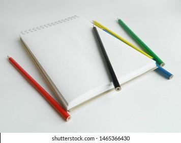 Clean sketchbook witn color pencils on white background