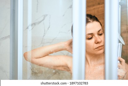 Clean up skin in doush with shower. Young woman portrait in domestic shower cabin.