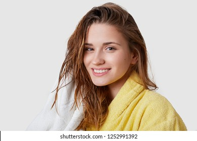 Clean smiling young female looks happily at camera, has tender smile, wet dark hair, wipes with towel, dressed in comfortable bathrobe, stands against white background. Human feelings, beauty concept