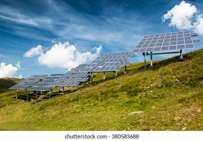 clean solar power panels on a nature green meadow in mountain scenery with blue sky and white clouds