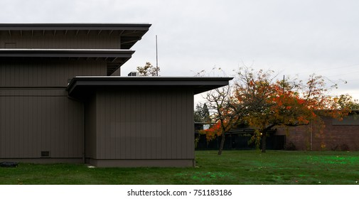 Clean straight architectural lines on this modern design in Eugene Oregon with grass and autumn trees, overcast sky