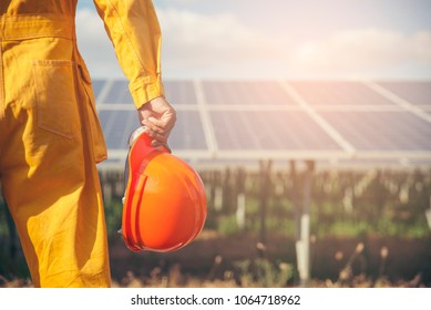 Clean and Sustainable Energy Concept.Electrical worker or engineer holding orange safety helmet work at solar panels background.Foreman wearing orange safety suit and looking at power plant.