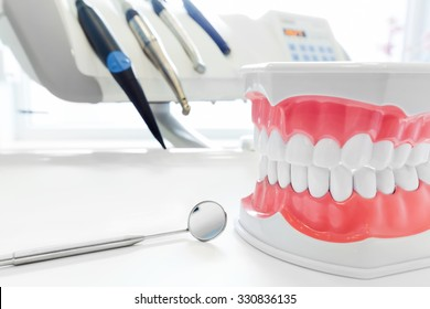 Clean teeth denture, dental jaw model, mirror and dentistry instruments in dentist's office.