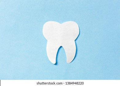Clean tooth on blue background. Concept healthy teeth or destruction enamel, decay, caries.
