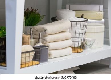 Clean towels, cups, soap dispenser, flowerpots, books, under bathroom white table.