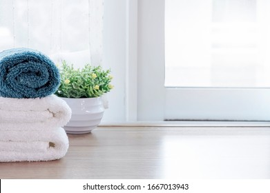 Clean towels and houseplant on wooden table near window sill in modern room. Copy space.